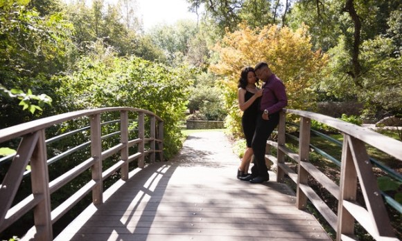 couple standing on a bridge in the woods