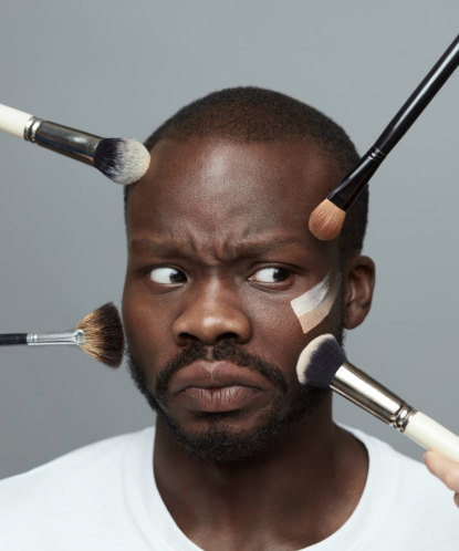 african man with makeup brushes on his face